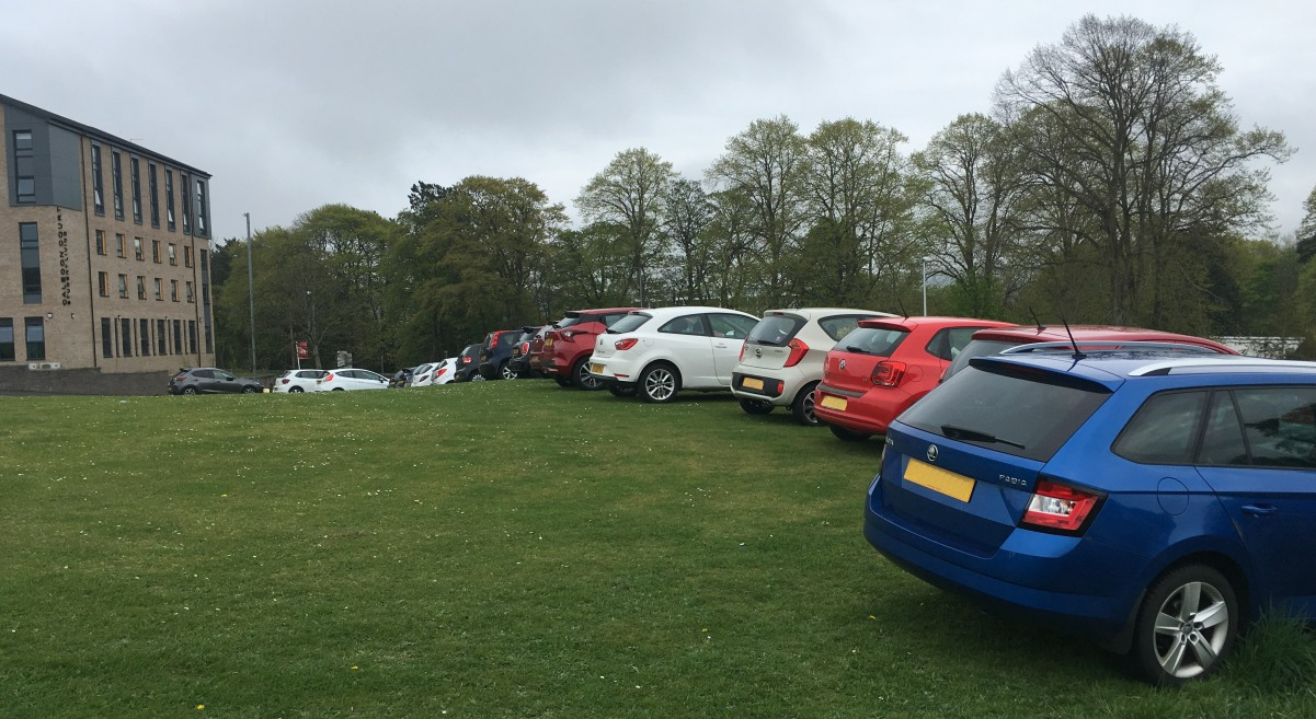 Photo of cars parked on grass area