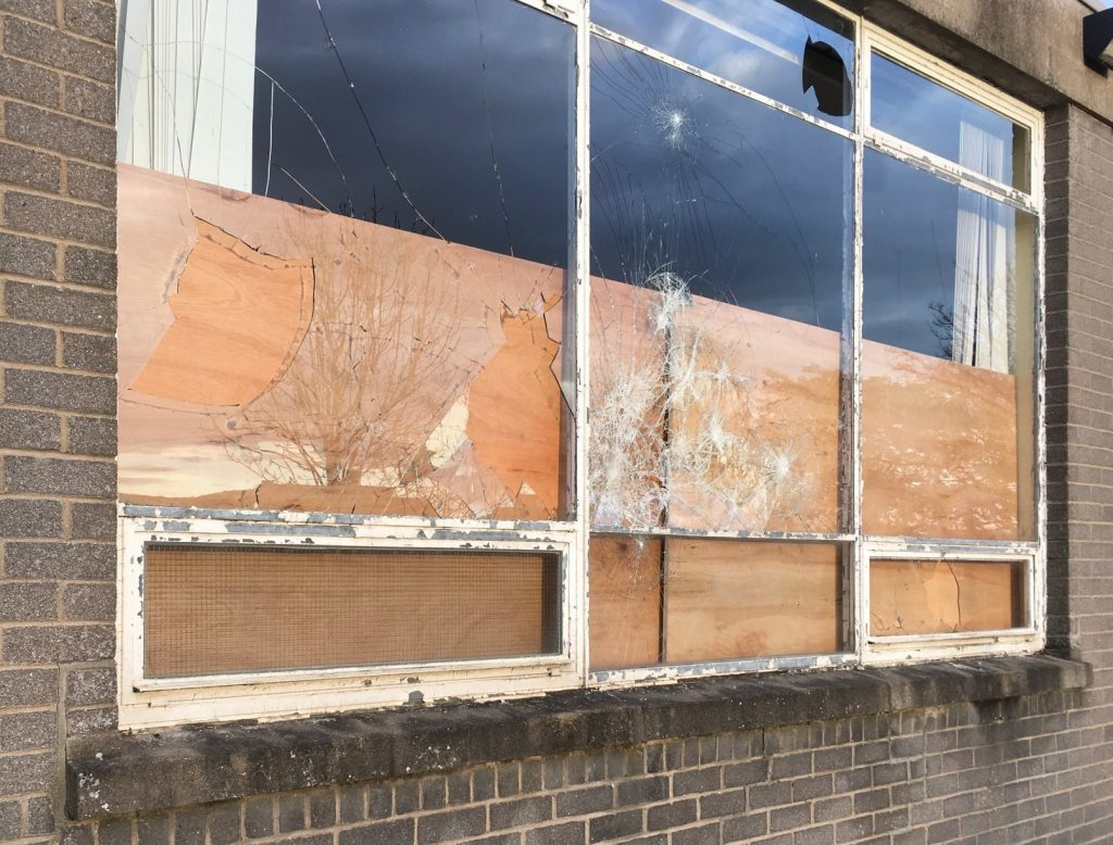 Photo of vandalised and boarded up window at Braeside School